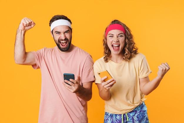 Retrato de um jovem casal feliz e esportivo usando faixas na cabeça, regozijando-se ao usar telefones celulares