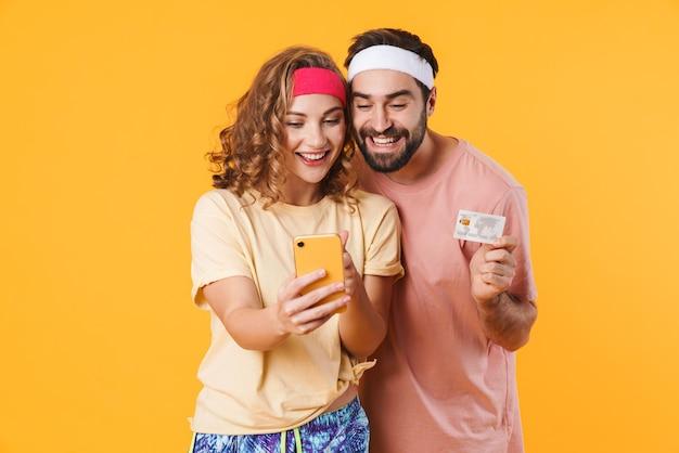 Retrato de um jovem casal feliz e esportivo usando tiaras, segurando o celular e o cartão de crédito isolados