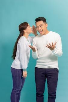 Retrato de um jovem casal feliz em pé sobre o azul, contando segredos