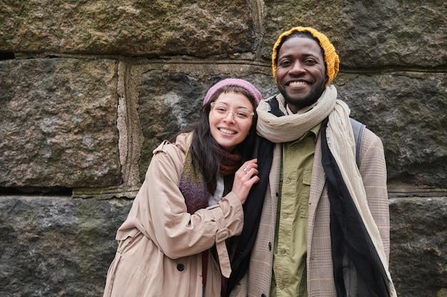 Retrato de um jovem casal feliz em roupas quentes, sorrindo para a câmera em pé na cidade