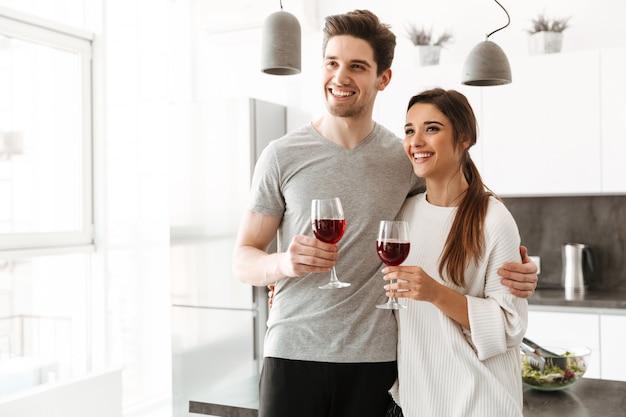 Retrato de um jovem casal feliz, segurando copos de vinho