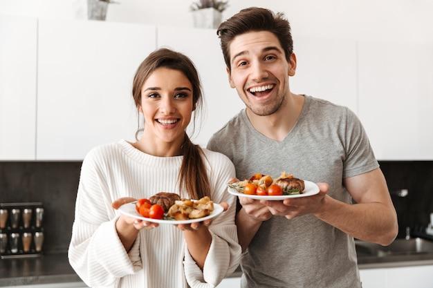 Retrato de um jovem casal feliz, segurando pratos