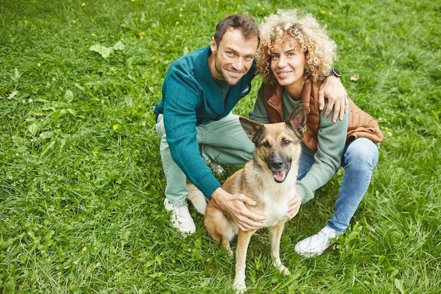 Retrato de um jovem casal feliz sentado na grama verde com o pastor alemão e sorrindo para a câmera