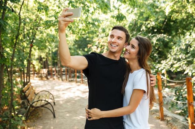 Retrato de um jovem casal feliz tomando uma selfie