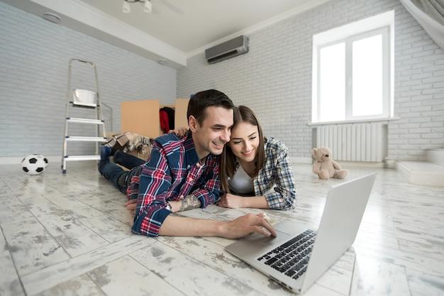 Retrato de um jovem casal fofo deitado no chão em um laptop de casa
