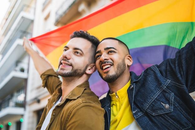 Retrato de um jovem casal gay abraçando e mostrando seu amor com a bandeira do arco-íris na rua. lgbt e conceito de amor.