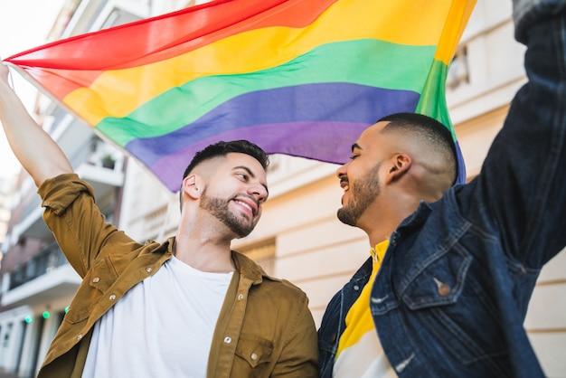 Retrato de um jovem casal gay, abraçando e mostrando seu amor com a bandeira do arco-íris na rua. lgbt e conceito de amor.