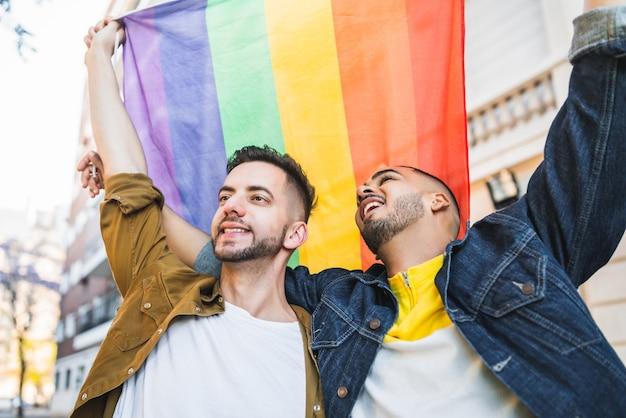 Retrato de um jovem casal gay abraçando e mostrando seu amor com a bandeira do arco-íris na rua. lgbt e o conceito de amor.
