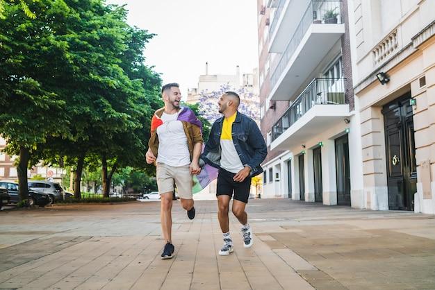Retrato de um jovem casal gay de mãos dadas e correndo junto com a bandeira do arco-íris na rua. lgbt e conceito de amor.