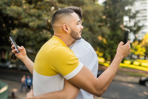 Retrato de um jovem casal gay se abraçando, cada um usando seu smartphone. problema de casal e conceito lgbt.