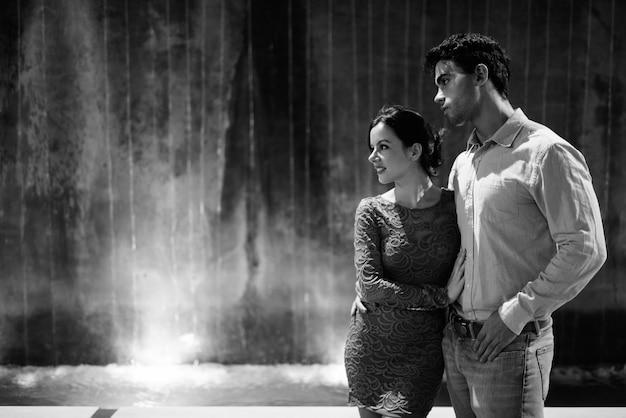 Retrato de um jovem casal hispânico explorando juntos as ruas da cidade à noite