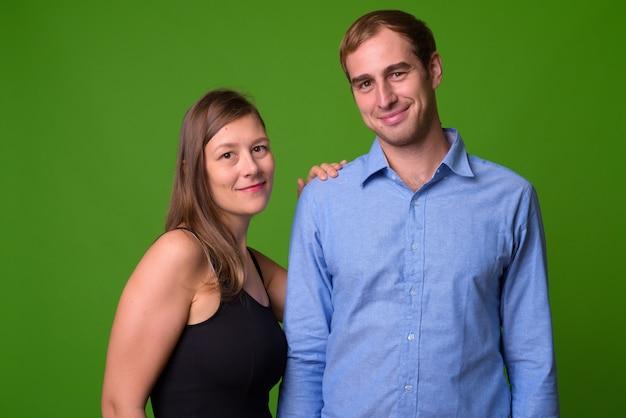 Retrato de um jovem casal junto à parede verde