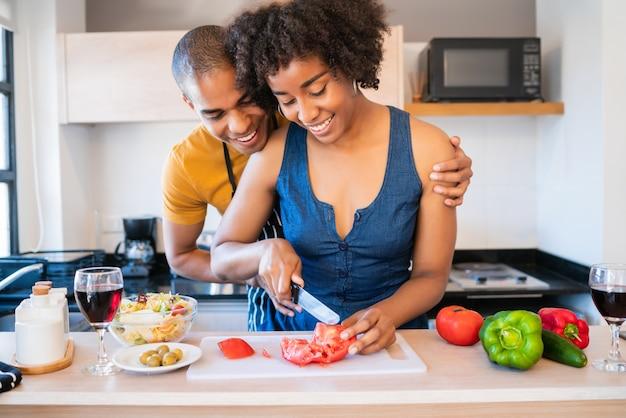 Retrato de um jovem casal latino cozinhando juntos na cozinha em casa. conceito de relacionamento, cozinheiro e estilo de vida.