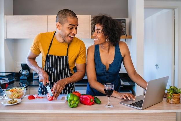 Retrato de um jovem casal latino usando um laptop enquanto cozinha na cozinha em casa. conceito de relacionamento, cozinheiro e estilo de vida.