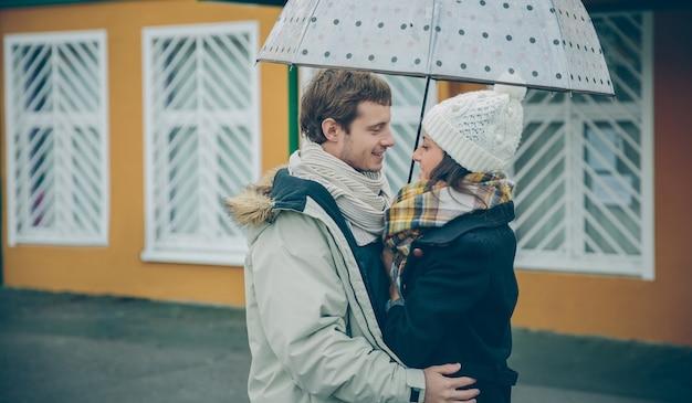 Retrato de um jovem casal lindo abraçando sob o guarda-chuva em um dia chuvoso de outono. amor e conceito de relacionamentos de casal.