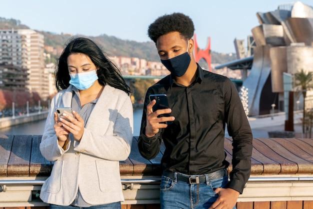 Retrato de um jovem casal na rua usando seu telefone celular escrevendo texto com máscaras devido à pandemia de coronavírus covid-19 de 2020 com cabelo estilo afro