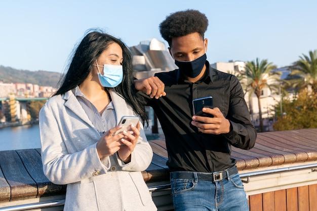Retrato de um jovem casal na rua usando seu telefone celular escrevendo texto com uma máscara facial devido à pandemia de coronavírus covid-19 de 2020 com cabelo estilo afro