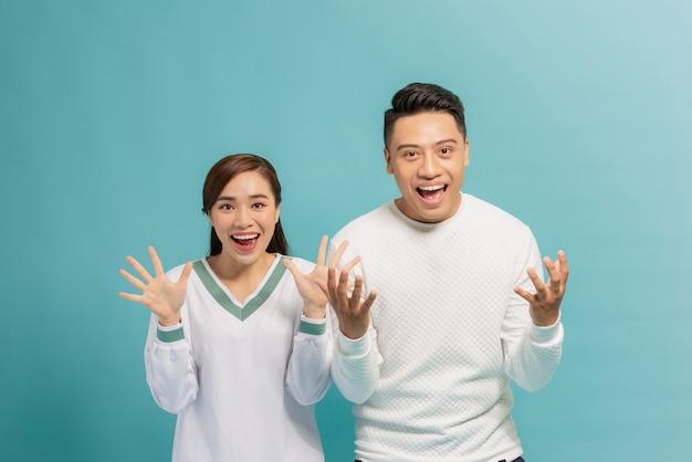 Retrato de um jovem casal otimista e surpreso, homem e mulher, com os braços erguidos, isolados sobre o azul