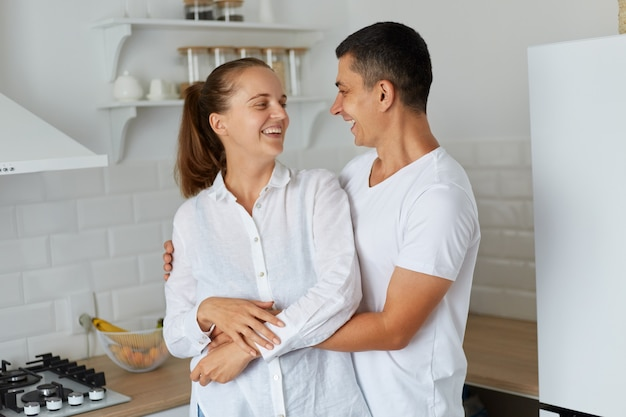 Retrato de um jovem casal se abraçando em casa com cozinha definida no fundo, marido e mulher, olhando um para o outro com amor e rindo, sendo felizes em ficar em casa sozinhos e passar algum tempo juntos.