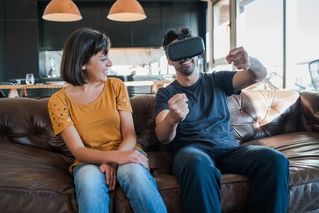 Retrato de um jovem casal se divertindo juntos e jogando videogame com óculos de realidade virtual enquanto está sentado no sofá em casa