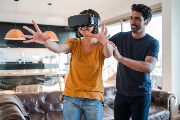 Retrato de um jovem casal se divertindo juntos e jogando videogame com óculos de realidade virtual enquanto fica em casa