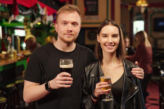 Retrato de um jovem casal segurando copos de cerveja e sorrindo para a câmera em pé no bar