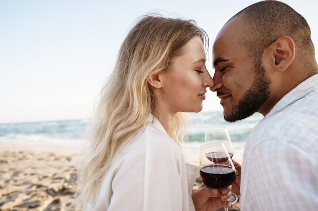 Retrato de um jovem casal sentado na praia bebendo vinho, close-up