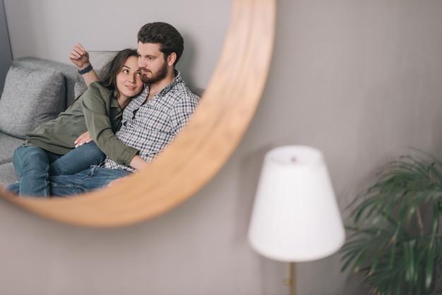 Retrato de um jovem casal sentado no sofá da sala de estar