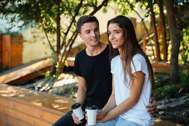 Retrato de um jovem casal sorridente bebendo café