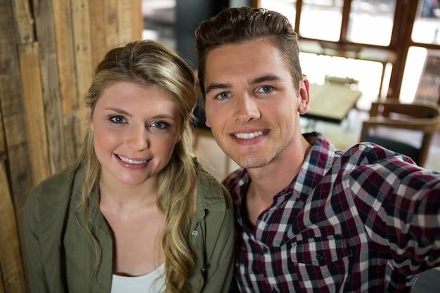 Retrato de um jovem casal sorridente, posando em uma cafeteria