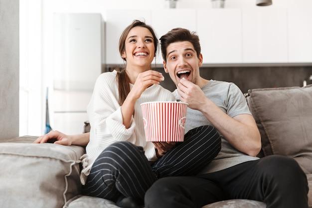 Retrato de um jovem casal sorridente, relaxando em um sofá