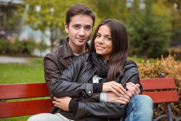 Retrato de um jovem casal sorridente, sentado no banco ao ar livre e olhando para a frente