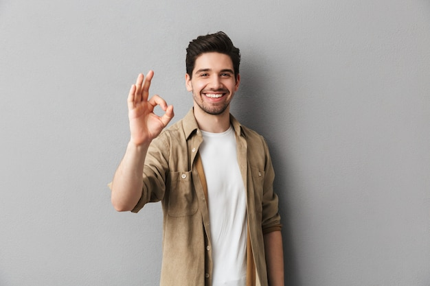 Retrato de um jovem casual feliz mostrando o gesto ok