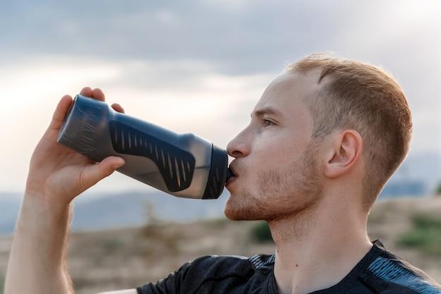Retrato de um jovem caucasiano beber água de uma garrafa antes ou antes do treino