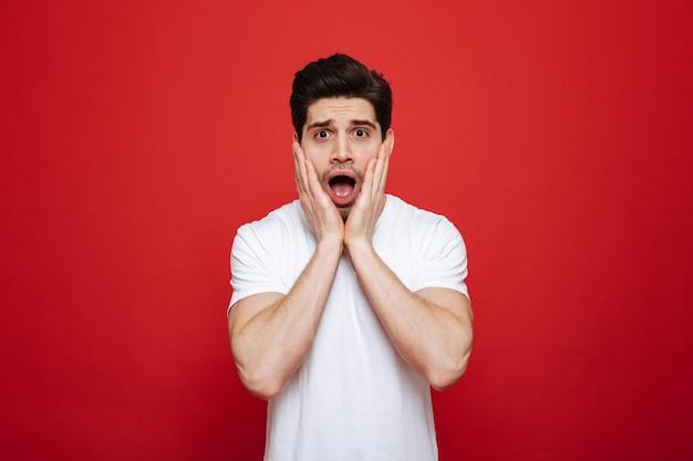 Retrato de um jovem chocado em camiseta branca