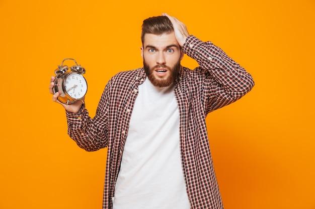 Retrato de um jovem chocado, vestindo roupas casuais, segurando um despertador