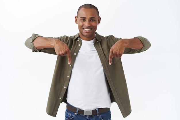 Retrato de um jovem cliente feliz do sexo masculino, homem afro-americano, convidando para se juntar à equipe, produto de check-out