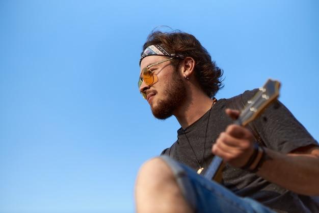 Retrato de um jovem com barba e óculos escuros que toca ukulele e olha para a distância.