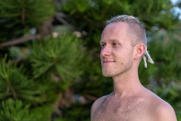 Retrato de um jovem com dreadlocks na cabeça na natureza. homem bonito feliz com dreadlocks na praia tropical, close-up