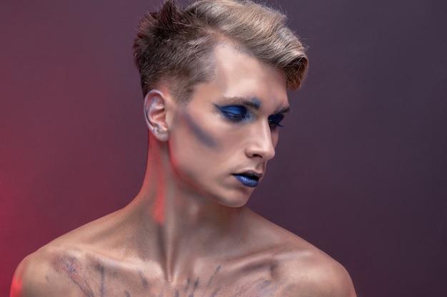 Retrato de um jovem com maquiagem profissional de beleza e cabelo loiro voador