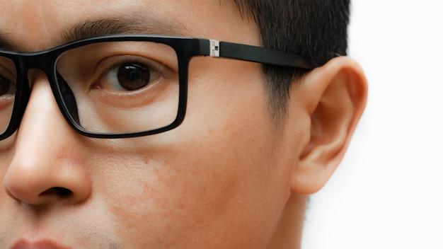 Retrato de um jovem com óculos, isolado no fundo branco.