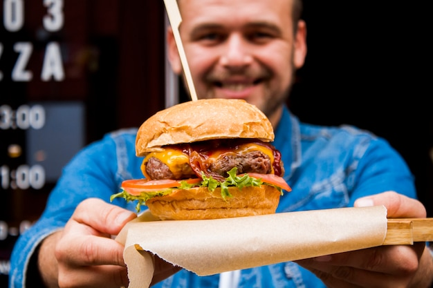Retrato de um jovem com um hambúrguer nas mãos dele.