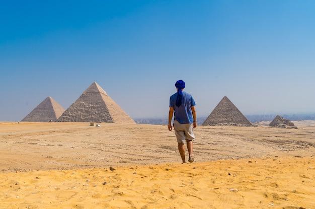 Retrato de um jovem com um turbante azul caminhando ao lado das pirâmides de gizé, cairo, egito