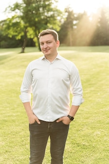 Retrato de um jovem com uma camisa branca, caminhando no parque ao pôr do sol. cara europeu olha para a câmera. homem no fundo do gramado do parque.