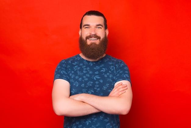 Retrato de um jovem confiante, sorrindo para a câmera sobre fundo vermelho.