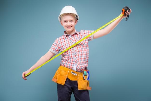Retrato de um jovem construtor em um capacete e uma fita métrica na mão