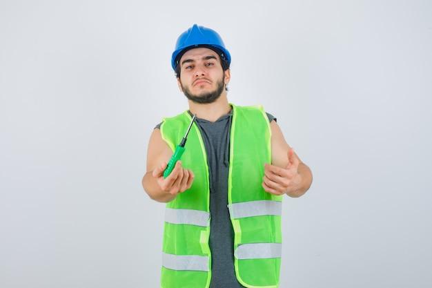 Retrato de um jovem construtor estendendo a mão para dar a chave de fenda de uniforme e olhando confiante para a frente