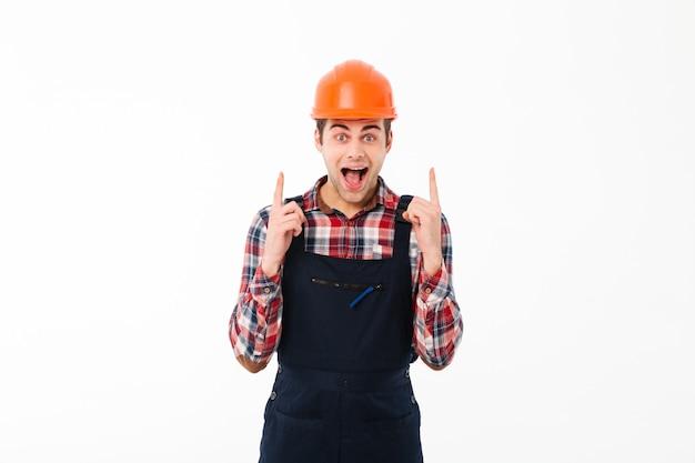 Retrato de um jovem construtor masculino animado apontando