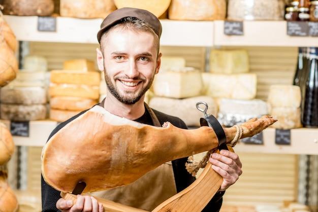 Retrato de um jovem contador com perna de prosciutto parado em frente a vitrine cheia de queijos