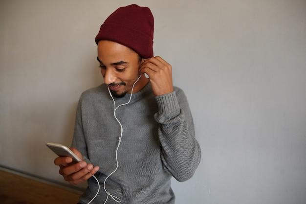 Retrato de um jovem de aparência agradável, de pele escura, com barba, ouvindo música com fones de ouvido e verificando suas redes sociais com smartphone